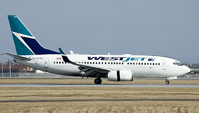 Westjet 737-700 landing at Montréal-Pierre Elliott Trudeau International Airport on a sunny Saturday afternoon.