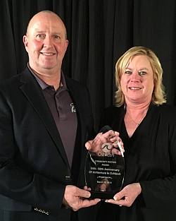 Dick Knapinski, EAA director of communications, and Karen Kryzaniak, EAA's vice president of risk management and human resources, accept the inaugural Community Partnership Award from the City of Oshkosh in recognition of 50 consecutive years of EAA fly-in conventions in the city.